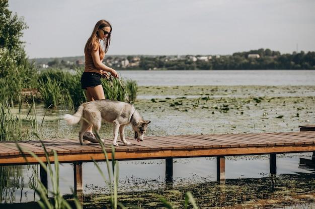 Jeune femme avec son chien husky au bord du lac