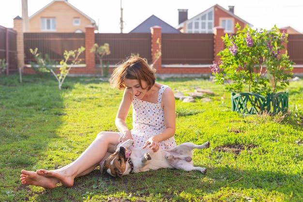 Jeune femme avec son chien jack russell terrier jouant sur l'herbe à l'extérieur