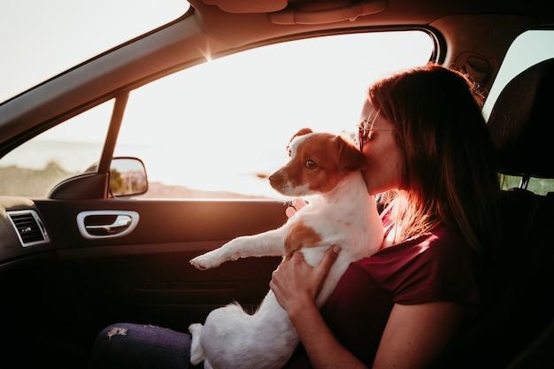 Jeune femme et son chien mignon dans une voiture au coucher du soleil. concept de voyage