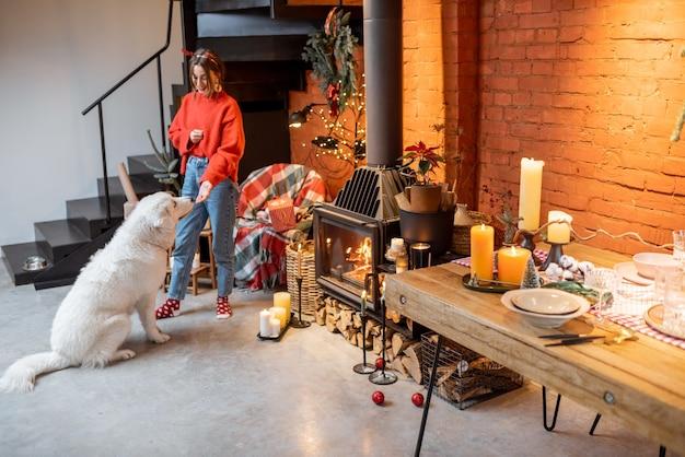 Jeune femme avec son chien mignon se préparant pour les vacances du nouvel an au coin du feu et table à manger à la maison