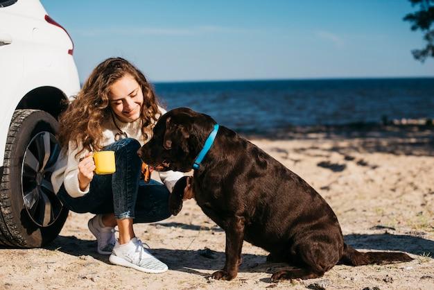 Jeune femme avec son chien à la plage