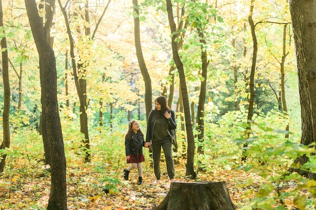 Jeune femme et son enfant fille marchant dans le parc concept de parent seul et de maternité
