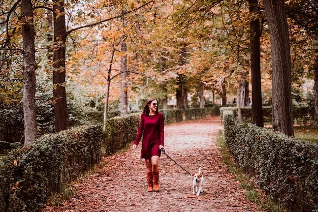 Jeune femme et son joli chien jack russell marchant dans un parc