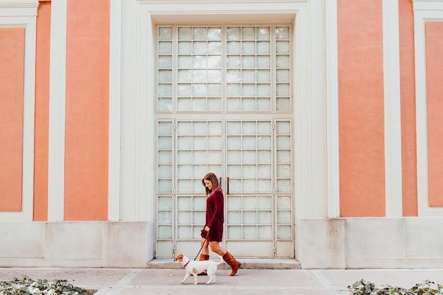 Jeune femme et son joli chien jack russell marchant près de la ville