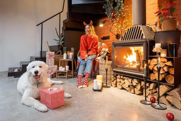 Jeune femme avec son mignon chien blanc déballant des coffrets cadeaux près d'une cheminée pendant de bonnes vacances du nouvel an à la maison