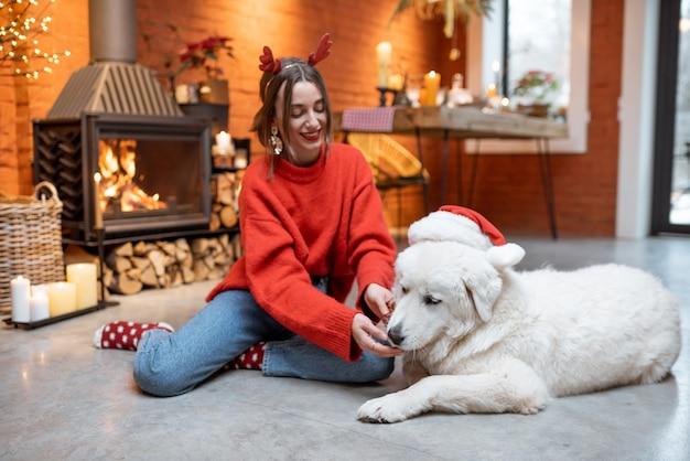 Jeune femme avec son mignon chien blanc pendant de joyeuses fêtes du nouvel an assis près d'une cheminée à la maison
