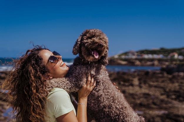 Jeune femme et son mignon chien d'eau espagnol à l'extérieur profiter ensemble par une journée ensoleillée et venteuse.