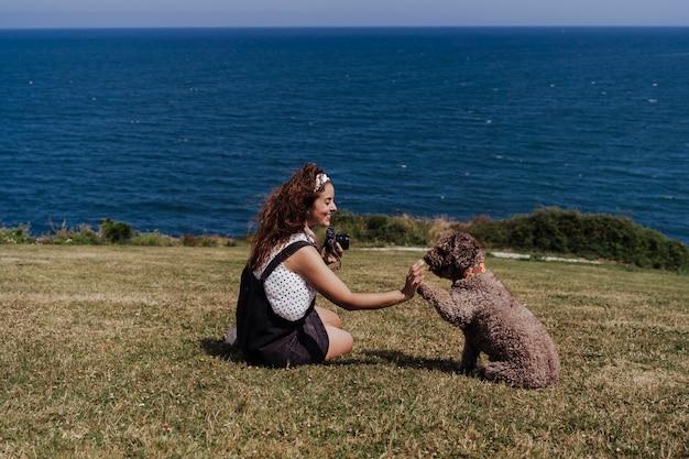 Jeune femme et son mignon chien d'eau espagnol profiter ensemble à l'extérieur par une journée ensoleillée.