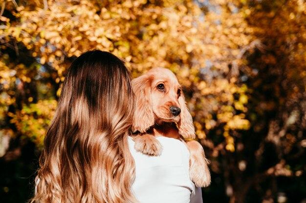 Jeune femme et son mignon chiot cocker spaniel chien à l'extérieur dans un parc. temps ensoleillé.