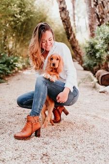 Jeune femme et son mignon chiot de cocker spaniel à l'extérieur dans un parc