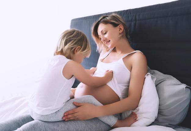 Jeune femme avec son premier enfant pendant la deuxième grossesse famille heureuse attend bébé