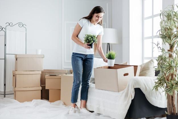 Une jeune femme sort ses plantes préférées d'une boîte en carton. emménager dans un nouvel appartement
