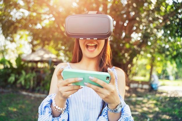Jeune femme sortie en utilisant un casque vr avec un téléphone portable.