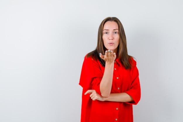 Jeune femme soufflant un baiser d'air avec des lèvres boudées en blouse rouge et l'air paisible, vue de face.