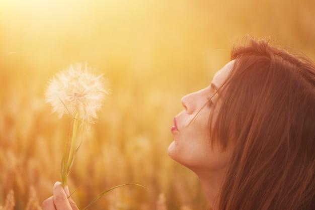 Jeune femme soufflant pissenlit dans le paysage d'automne au coucher du soleil