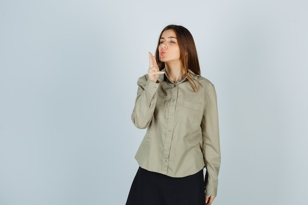 Jeune femme soufflant sur un pistolet à doigt avec des lèvres boudeuses en chemise, jupe et l'air confiant. vue de face.