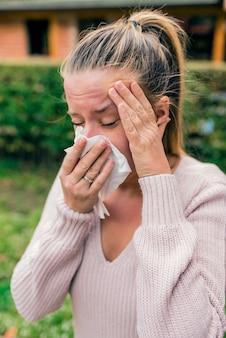 Jeune femme souffle son nez. rhinite allergique.