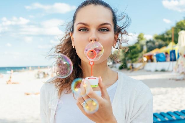 Jeune femme souffler des bulles sur la plage en été