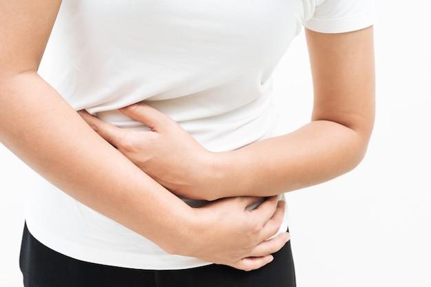 Jeune femme souffrant de douleurs abdominales, sensation de mal de ventre, symptôme de pms sur fond blanc