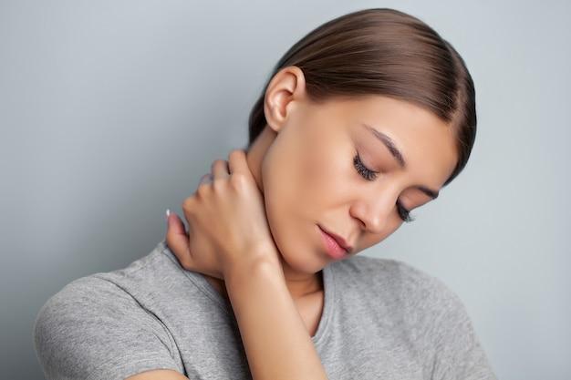 Jeune femme souffrant de graves douleurs au cou tout en tenant ses mains.