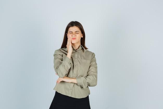 Jeune femme souffrant de maux de dents en chemise, jupe et à la douleur