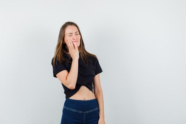 Jeune femme souffrant de maux de dents en chemisier noir, pantalon et à l'air troublé.