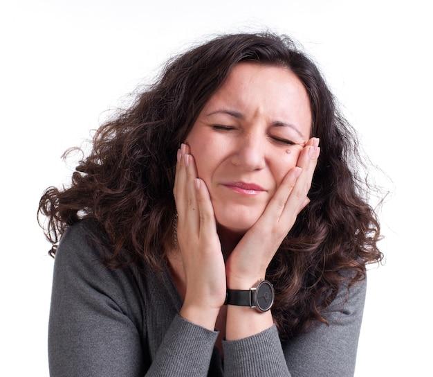 Jeune femme souffrant de maux de dents sur fond blanc