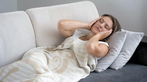 Jeune femme souffrant de maux de tête allongée sur un canapé avec les yeux fermés