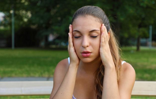 Jeune femme souffrant de maux de tête à l'extérieur.