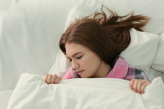 Jeune femme souffrant de troubles du sommeil au lit à la maison