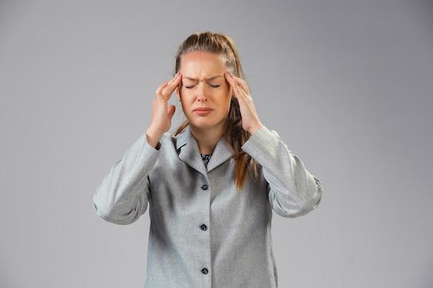 Une jeune femme souffre de douleur, se sent malade et la faiblesse est isolée sur le mur