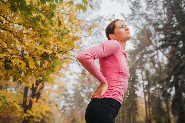 La jeune femme souffre de douleurs au dos. elle se tient dans le parc d'automne et lève les yeux. la femme souffre.