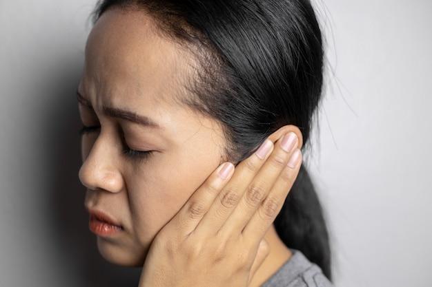 La jeune femme souffre de maux d'oreille.