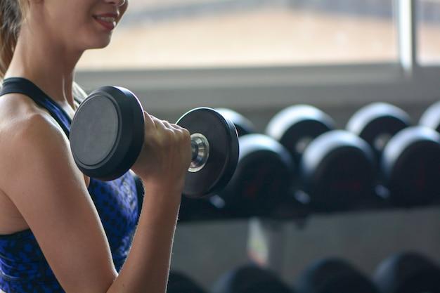 Jeune femme soulever des haltères, concept de fitness gym.