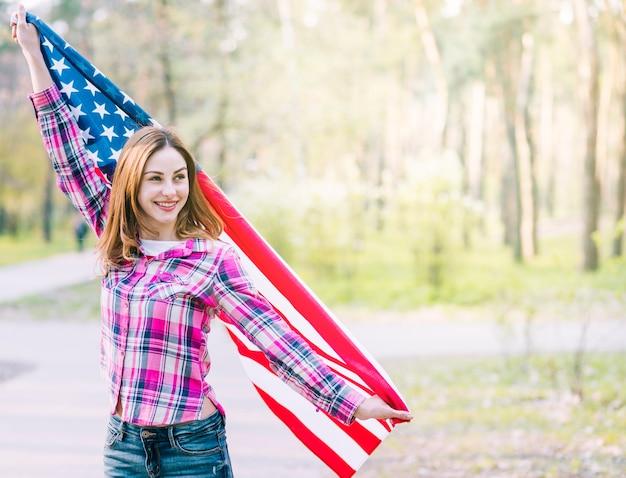 Jeune femme souriante, agitant un drapeau américain dans le parc