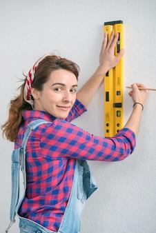 Jeune femme souriante à l'aide d'un niveau à bulle