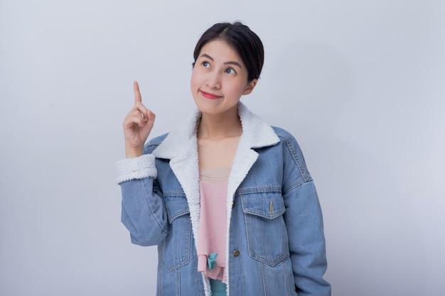 Jeune femme souriante asiatique pointent sa main à l'arrière-plan, positive fille caucasienne heureuse portant portrait de vêtements décontractés bleu