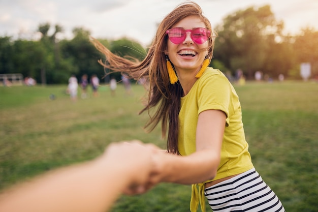 Jeune femme souriante assez élégante s'amusant dans le parc de la ville, tenant la main de son petit ami, suivez-moi, positive, émotionnelle, portant haut jaune, lunettes de soleil roses, tendance de la mode estivale, émotion positive