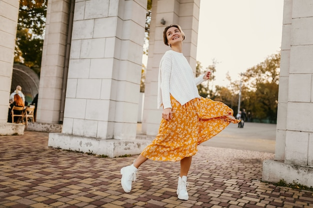 Jeune femme souriante assez heureuse en robe imprimée jaune et pull blanc tricoté le jour d'automne ensoleillé s'amusant dans la rue portant une tenue élégante et des bottes blanches