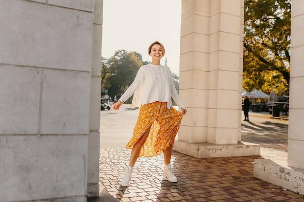Jeune femme souriante assez heureuse en robe imprimée jaune et pull blanc tricoté le jour d'automne ensoleillé