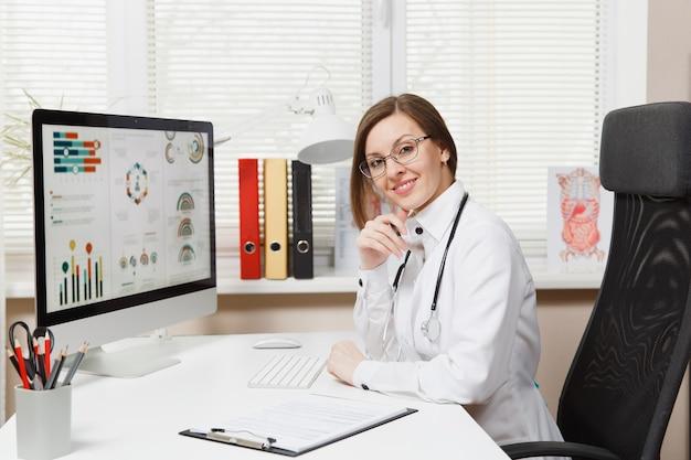 Jeune femme souriante assise au bureau, travaillant sur ordinateur avec des documents médicaux dans un bureau léger à l'hôpital