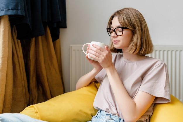 Jeune femme souriante assise dans l'appartement portant un jean bleu tshirt rose et des lunettes tenant une tasse