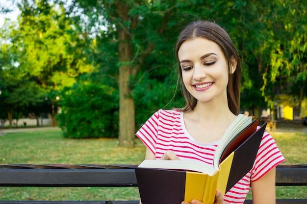 Jeune femme souriante assise avec journal prenant des notes dans le magnifique parc de la ville