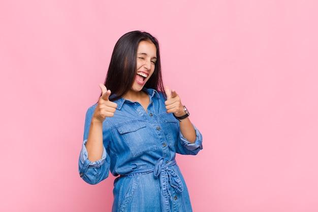Jeune femme souriante avec une attitude positive, réussie et heureuse, pointant vers la caméra, faisant signe des armes à feu avec les mains
