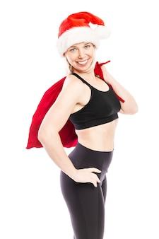 Jeune femme souriante au chapeau de père noël, sac rouge avec des cadeaux et dans un costume de fitness noir. isolé sur fond blanc. ambiance festive. verticale.
