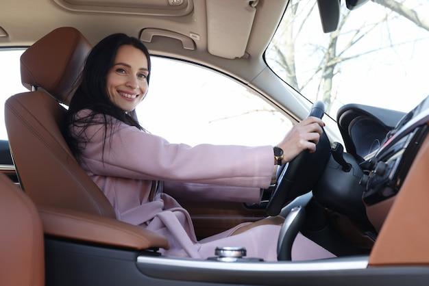 Jeune femme souriante au volant d'une voiture de luxe en gros plan