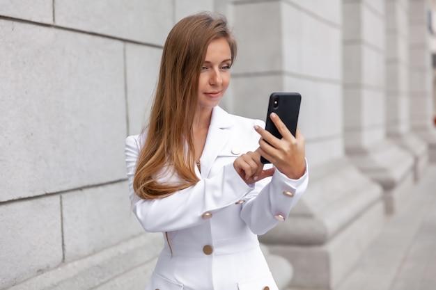 Jeune femme souriante en blouse blanche à l'aide de smartphone