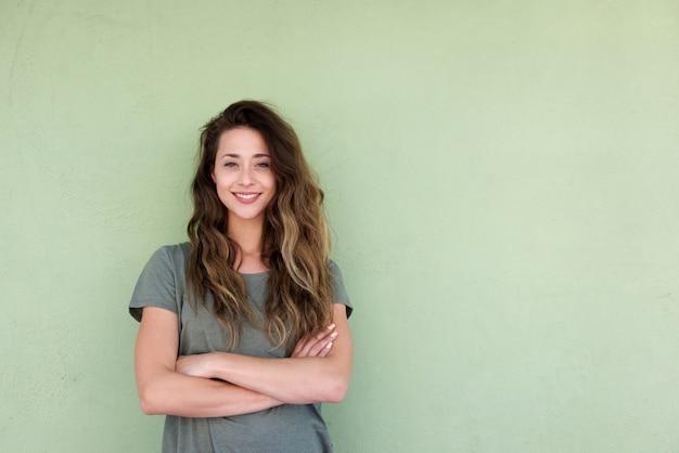 Jeune femme souriante avec les bras croisés sur fond vert