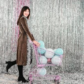 Jeune femme souriante avec caddie avec lampes décoratives près de tinsel