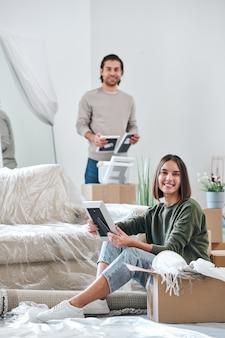 Jeune femme souriante avec cadre photo assis sur le sol et vous regarde pendant que son mari déballage des boîtes avec des trucs sur fond
